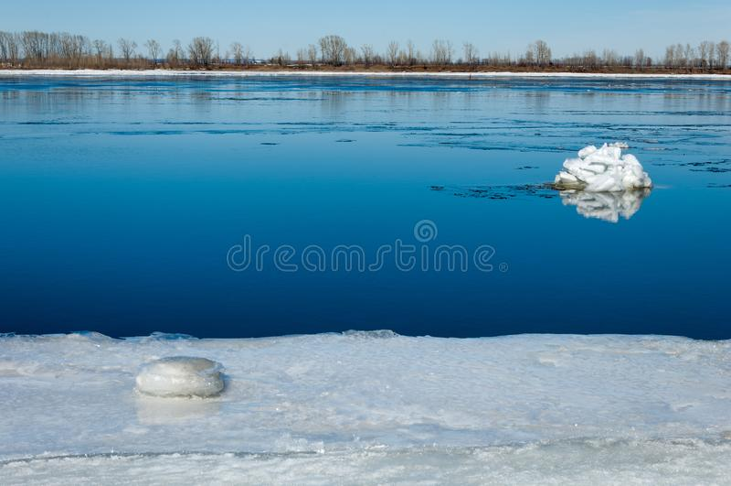 Rivier met gebroken ijs ijsheuveltjes op de rivier in de lente stock afbeelding
