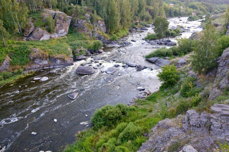 Rivier met stroomversnelling en rotsachtig hellingenlandschap van een de zomerzonsondergang, het Oeralgebergte stock afbeeldingen