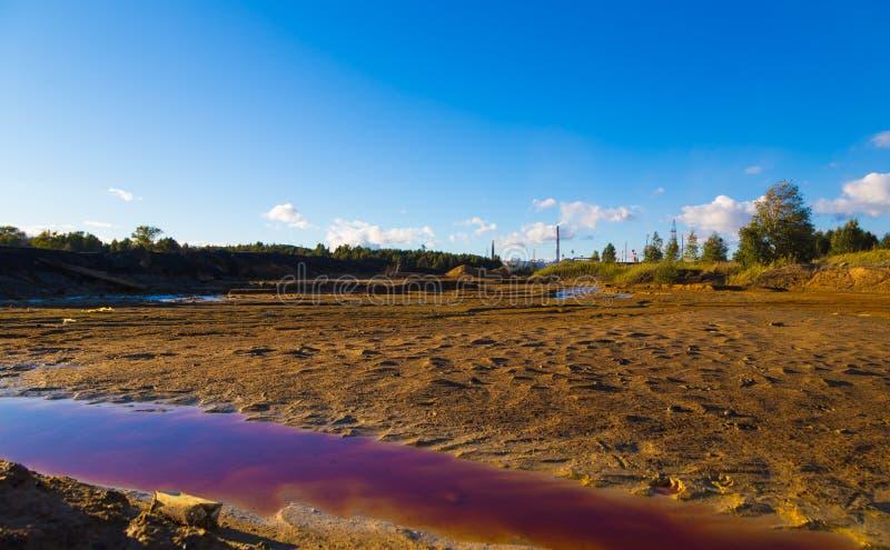 Rivier met verontreinigde rode giftige water en grond en met huisvuil op de kust milieuvervuiling door fabriek royalty-vrije stock foto's