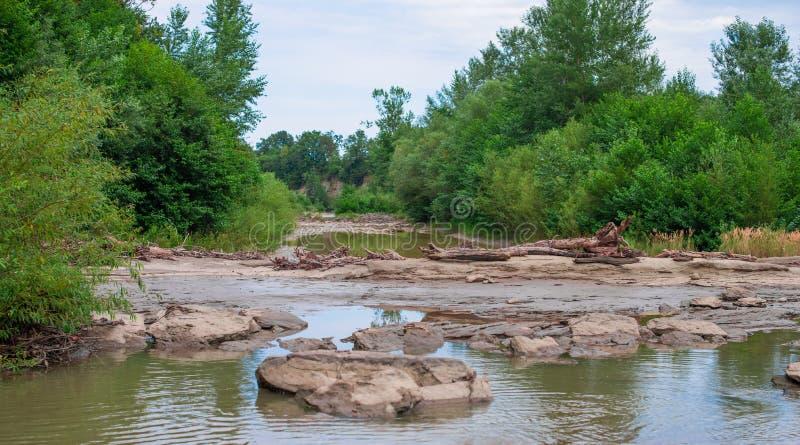 Rivierbed van een ondiepe rivier met een barrière van stenen stock foto