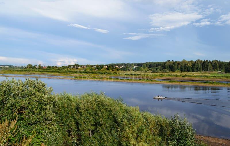 Rivierlandschap met een motorboot stock foto's
