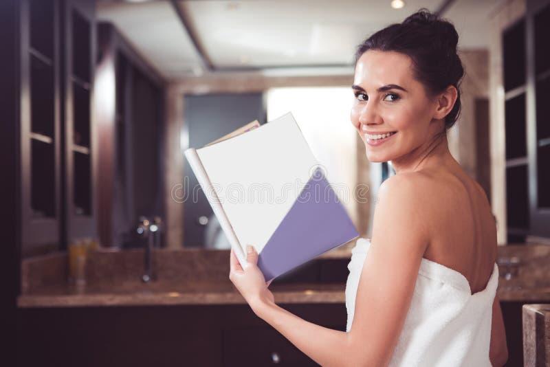 Rivista contentissima della tenuta della donna in bagno fotografia stock