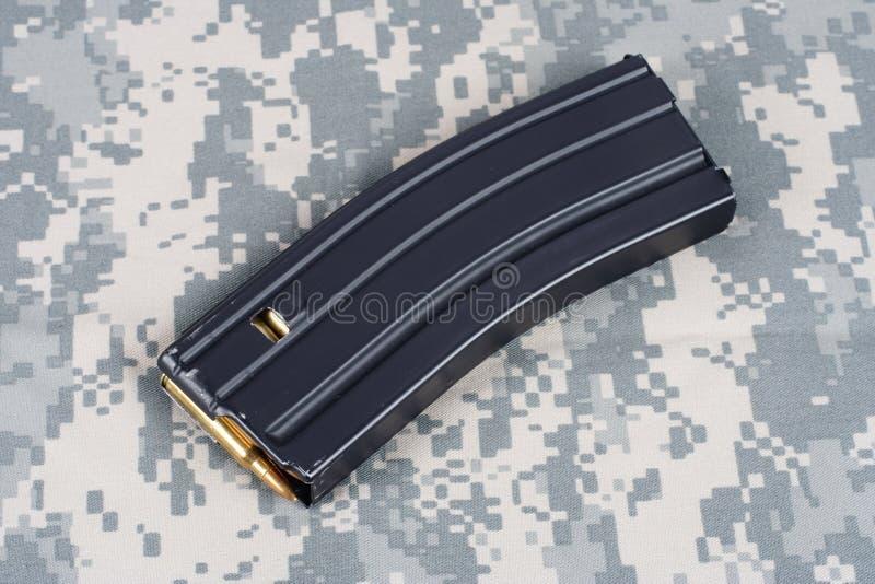 Rivista del fucile dell'ESERCITO AMERICANO M-16 con le cartucce sull'uniforme del cammuffamento immagini stock libere da diritti