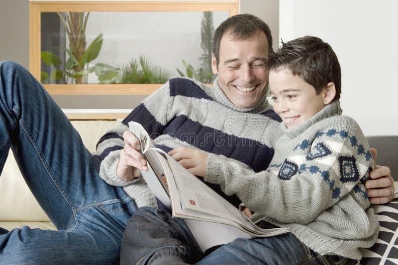 Rivista della lettura del bambino e del papà immagini stock libere da diritti