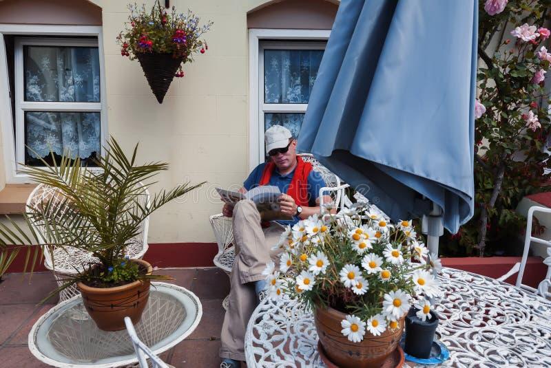 Rivista della lettura dell'uomo in giardino domestico fotografia stock