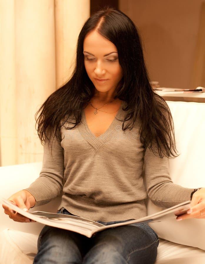 Rivista della lettura della giovane donna a casa immagine stock