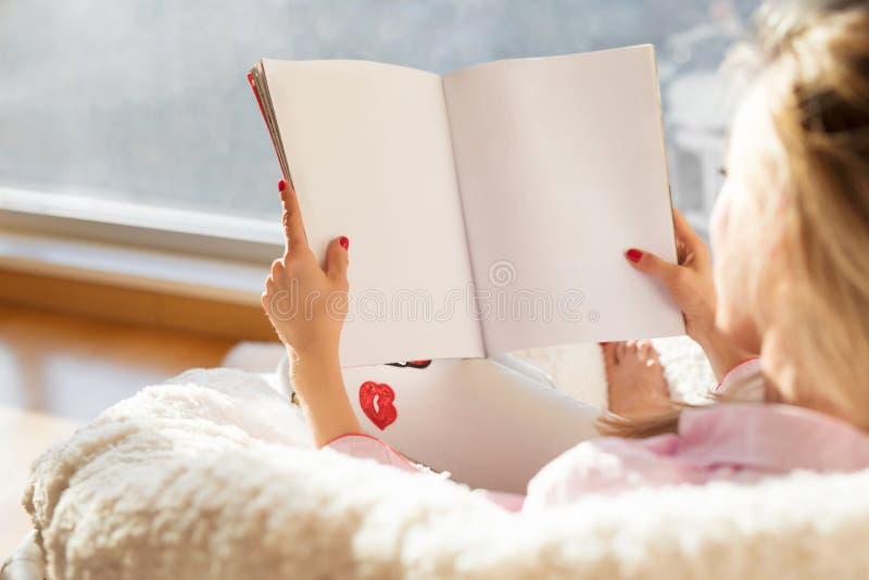 Rivista della lettura della donna con le pagine in bianco bianche vuote Modello per il vostri propri contenuto fotografia stock libera da diritti
