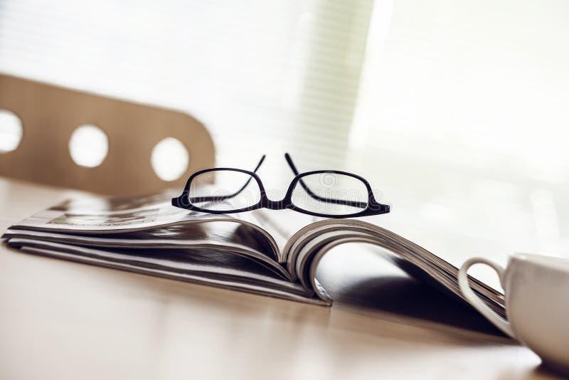 Rivista della lettura in ufficio fotografia stock