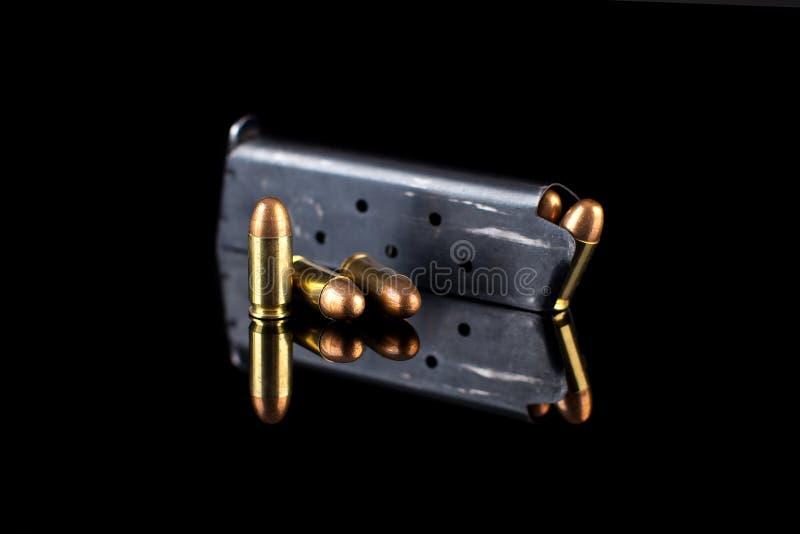 Rivista della pistola con munizioni sul nero fotografia stock