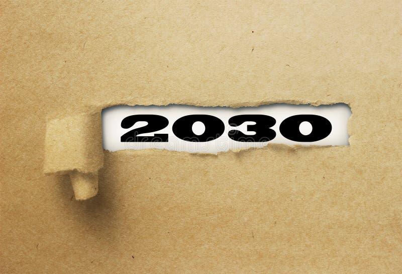 Rivit sönder eller sönderrivet papper som avslöjer det nya året 2030 på vitt royaltyfria bilder
