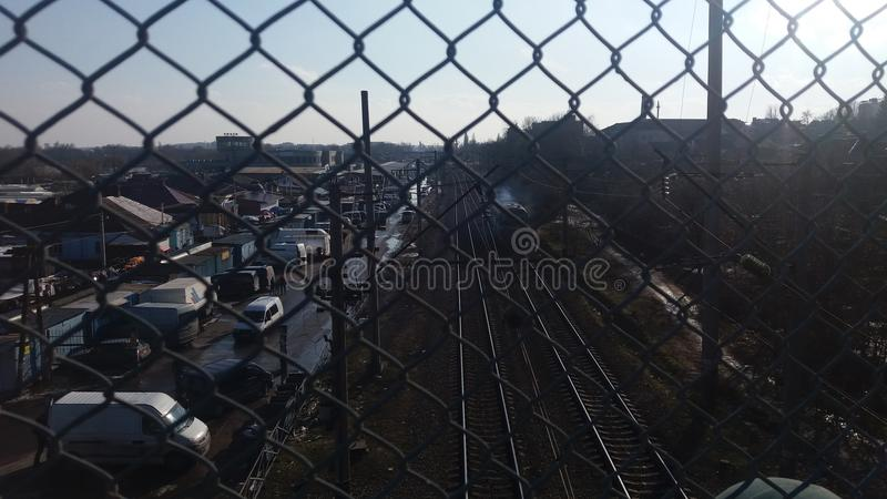 Rivne Ukraine. Railways view from the bridge. Rivne Ukraine. View from the bridge to the railways. Grid on the bridge. Many cars in Rivne. Market in Rivne royalty free stock image