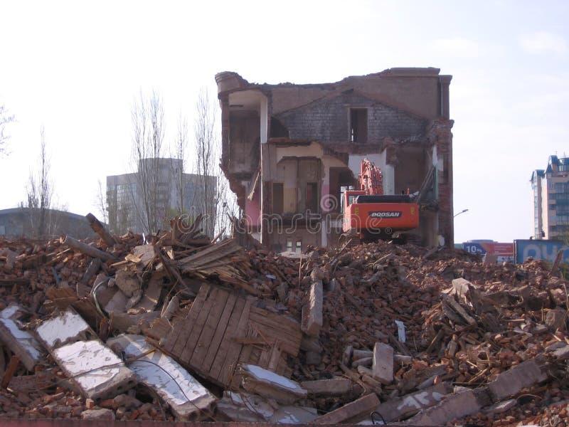 Rivning av den gamla byggnaden i Novosibirsk bland fördärvar av en grävskopa royaltyfri foto