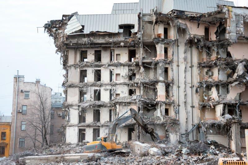 Rivning och förstörelse av en byggnad genom att använda grävskopan Jagareutrustning fotografering för bildbyråer