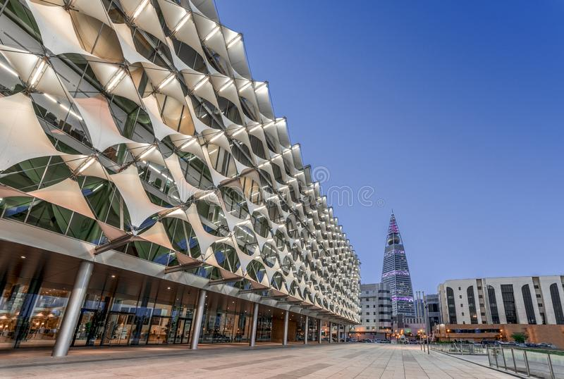 Riyadh Saudiarabien - Oktober 18, 2018: Perpective sikt av fasaden f?r konung Fahad National Library in mot Al Faisaliyah Tower royaltyfria bilder