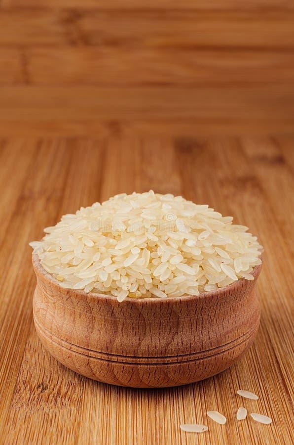 Riz blanc Basmati dans la cuvette en bois sur le panneau en bambou brun, plan rapproché image libre de droits