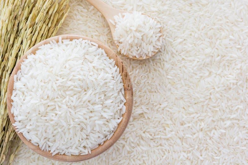 Riz blanc dans la cuvette et un sac, une cuillère en bois et usine de riz sur le fond de riz blanc image libre de droits