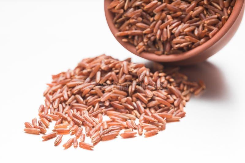 Riz brun cru dispersé hors d'une tasse de poterie de terre sur un fond blanc photos stock