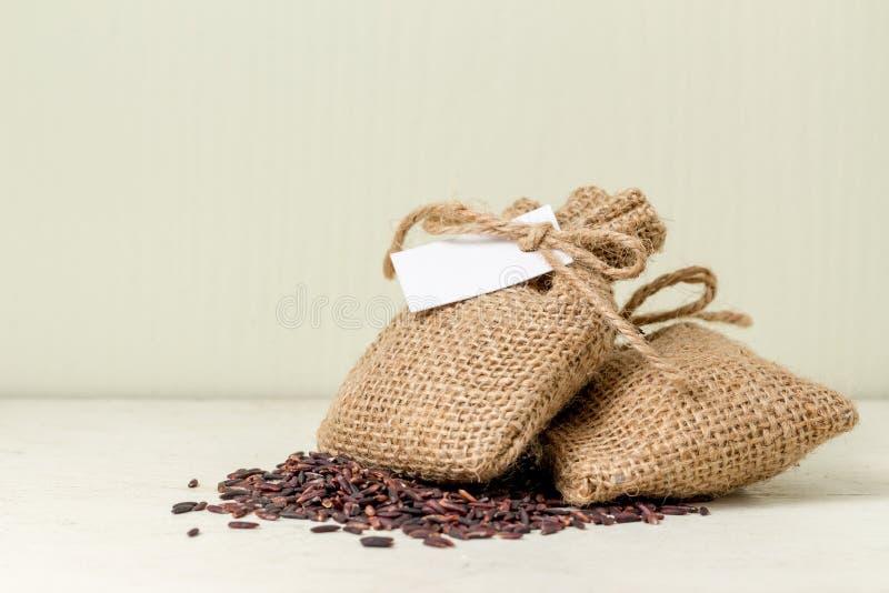 Riz brun dans le sac de sac sur le blanc de table photos libres de droits