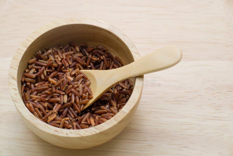 Riz brun, dans une cuvette en bois avec la cuillère en bois sur le backgroun en bois photo libre de droits