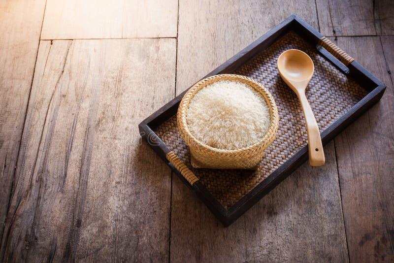 Riz dans le panier en bambou et cuillère en bois sur le sac de sac et Ba en bois photo libre de droits