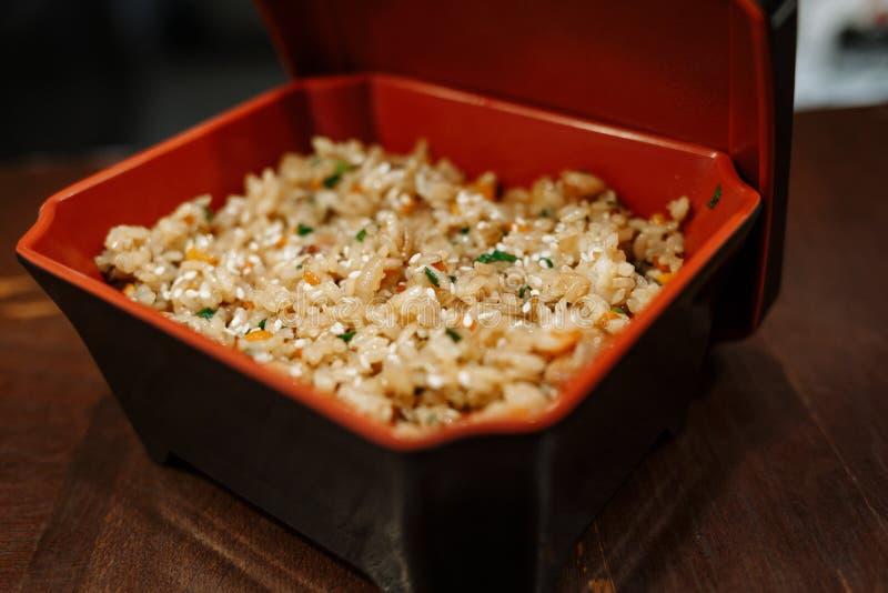 Riz frit avec des l?gumes dans une bo?te rectangulaire noire avec l'intestin rouge sur un fond en bois de table images stock