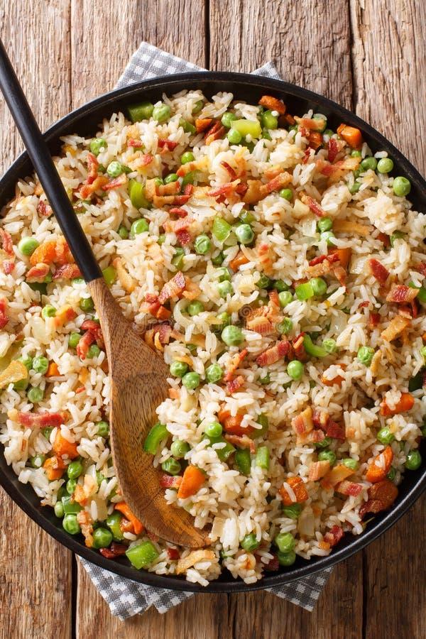 Riz frit avec légumes et bacon dans une assiette Vue verticale du haut photos stock