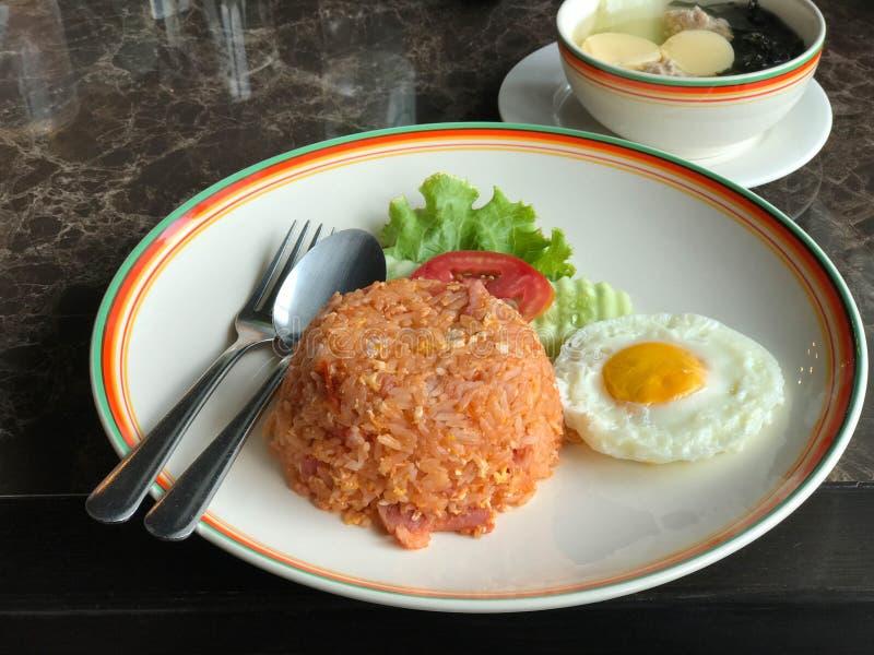 Riz frit de jambon et d'oeufs dans le plat avec l'oeuf au plat et la soupe image stock
