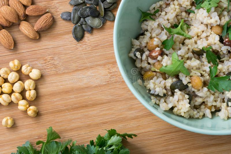 Riz intégral dans la cuvette verte, cuite avec l'amande, graines de citrouille, pois chiche et arrosée avec le persil sur le fo photographie stock