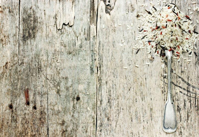 Riz mélangé dans la cuillère en métal de vintage sur le vieux fond en bois photographie stock libre de droits