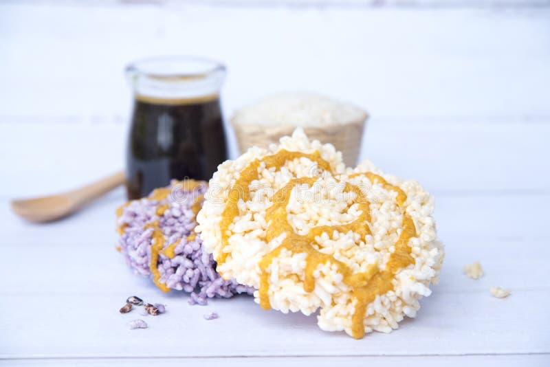 Riz soufflé doux avec le caramel dans une bouteille en verre sur la vieille table en bois blanche, desserts croustillants et thaï images libres de droits