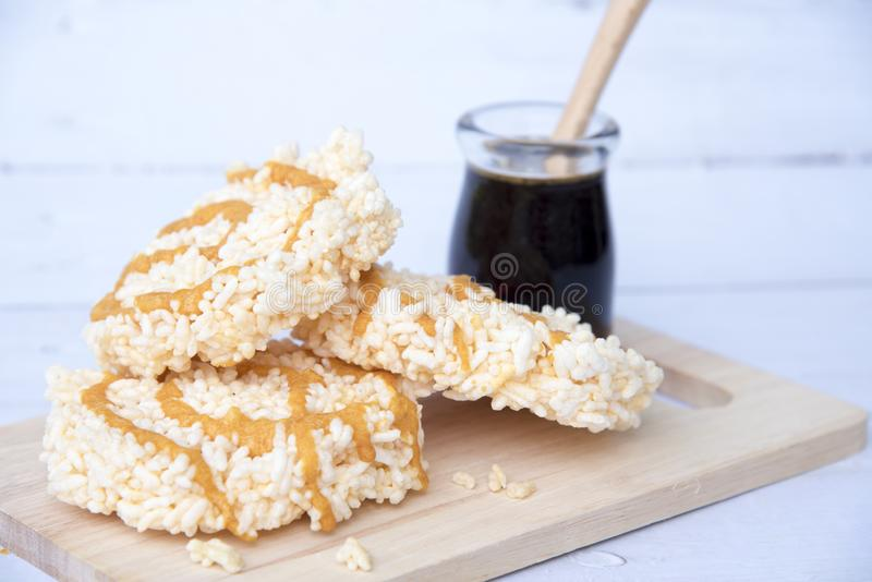 Riz soufflé doux avec le caramel dans une bouteille en verre sur la vieille table en bois blanche, desserts croustillants et thaï images stock