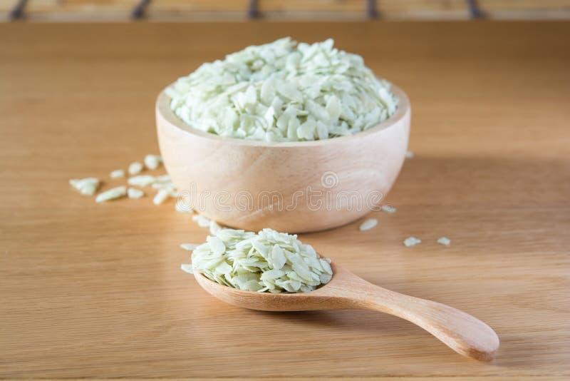 Riz vert dans une cuillère et une cuvette en bois photos stock