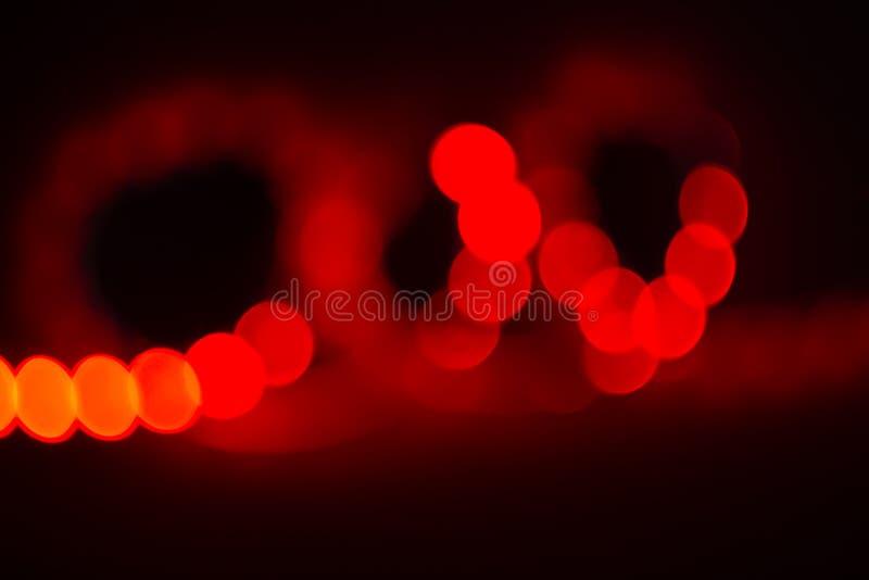 Rizos borrosos de neón rojos de las luces del bokeh en negro Fondo abstracto de los colores 80s imagenes de archivo