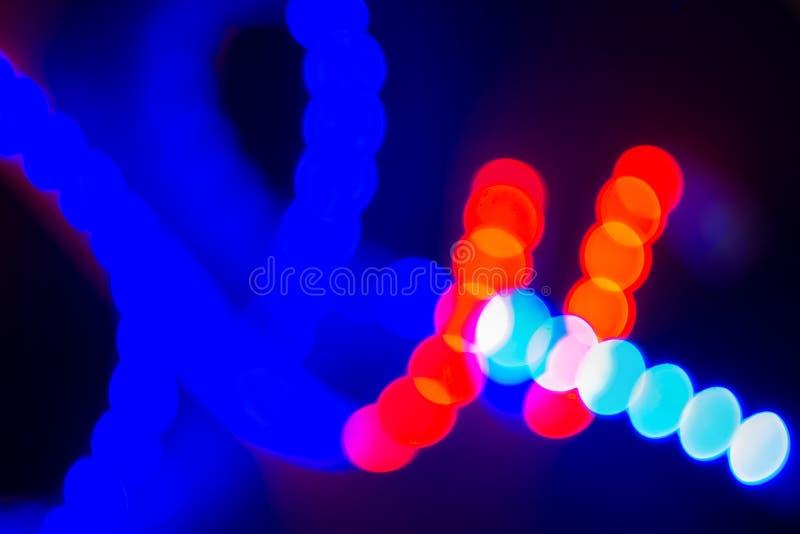 Rizos borrosos de neón rojos y azules de las luces del bokeh en negro Fondo abstracto de los colores 80s imágenes de archivo libres de regalías