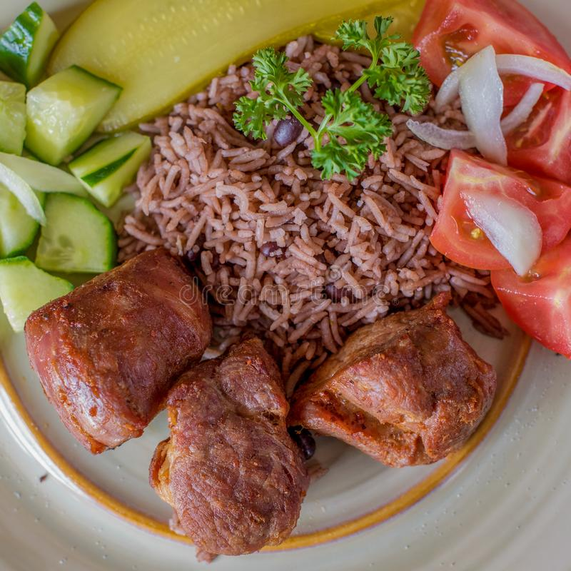 Cuban cuisine: deep fried pork meat with congri rice. And salad. Typical creole cuisine stock photography