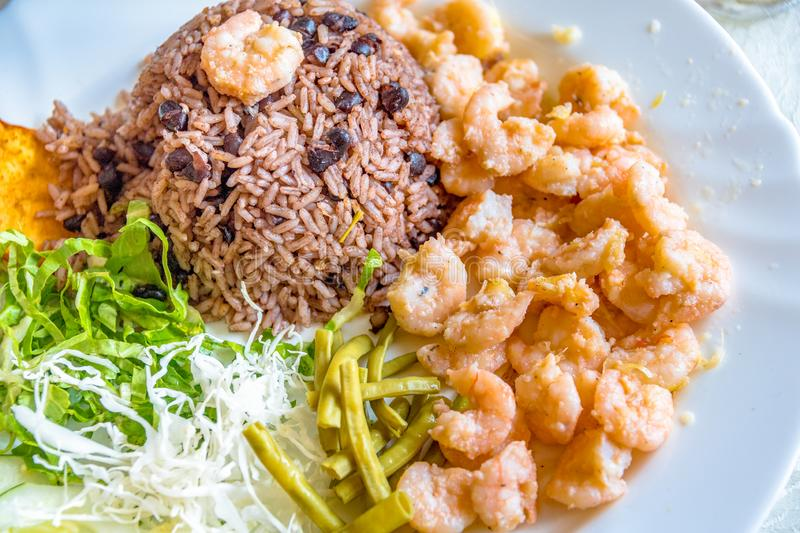 Garlic shrimp dish with congri rice. Cuban cuisine in plate containing rice, prawns and salads. The meal is served at a privately owned restaurant at an royalty free stock photos