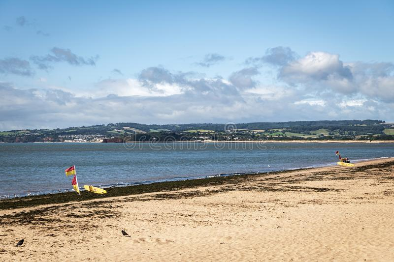 RNLI Safe swimming. Area marked out by red and yellow flags and surfboards on Exmouth beach, Devon, England royalty free stock photos