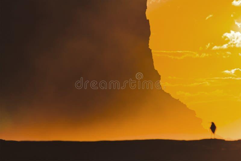 RNP Garie Cliff Sun Bird Corner. Small seabird standing on a coastal boulder under distant headland cliff in warm orange sunbeams of rising sun at Garie Beach in royalty free stock photo