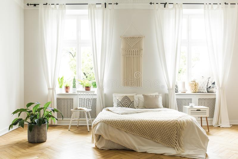 Roślina i bielu krzesło obok łóżka z koc w jaskrawej sypialni zdjęcie stock