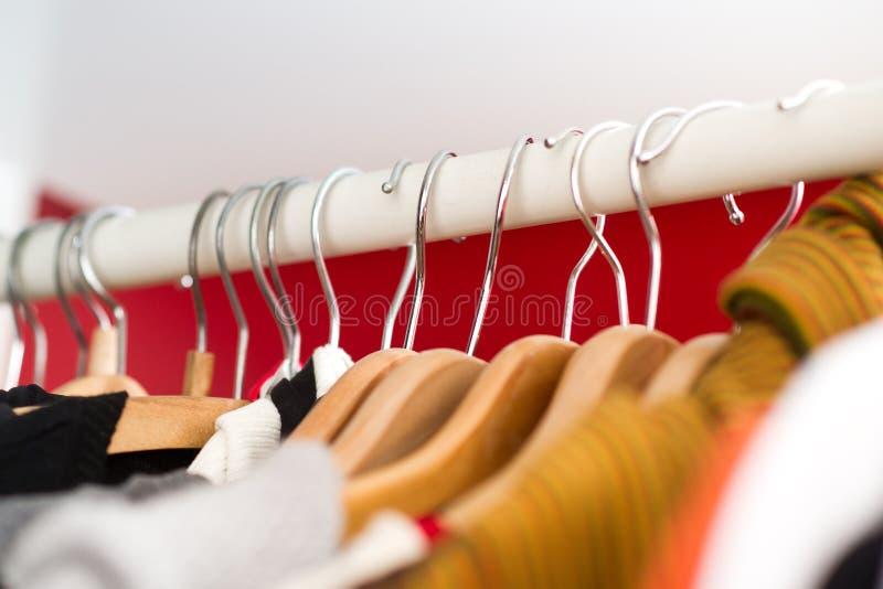 Ro av kvinna kläder som hänger i garderob arkivbilder