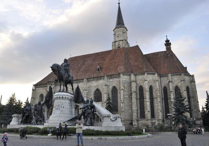 RO de Cluj-Napoca, o 23 de setembro: Matei Corvin Monument e igreja St Michael em Cluj-Napoca da região da Transilvânia em Romêni imagem de stock royalty free
