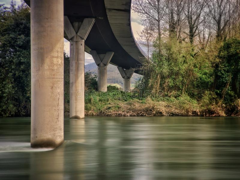 Road above the river in central Asturias. Spain. Road above the river in central Asturias. Round concrete columns and large flow of water in a wooded environment royalty free stock photography