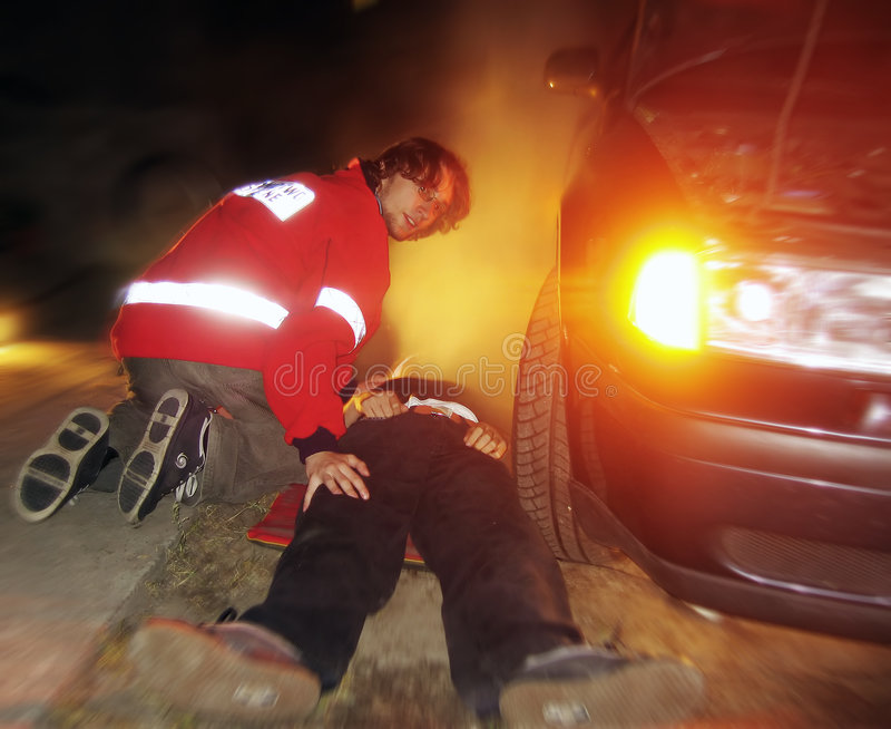 Road accident. MD/paramedic is helping hurt victim of accident royalty free stock photos