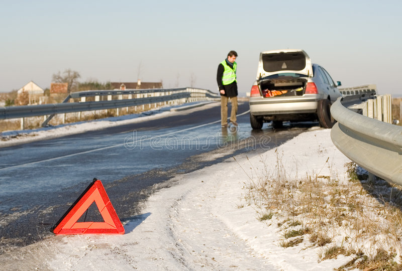 Road accident. Warning triangle and driver in a reflective safety vest near the broken car. Focus on triangle stock images