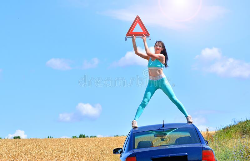 Road accident concept. The woman got into a traffic accident and needs help. Girl stands on a car roof and holds red warning triangle royalty free stock image