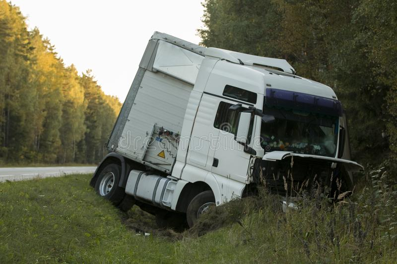 Road accident lorry car crash on an highway lane road. Automobile in side ditch royalty free stock photo