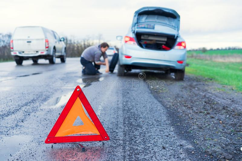 Road accident sign on the background man replaces flat tyre on road. Car tire leak because of nail pounding.  stock photos