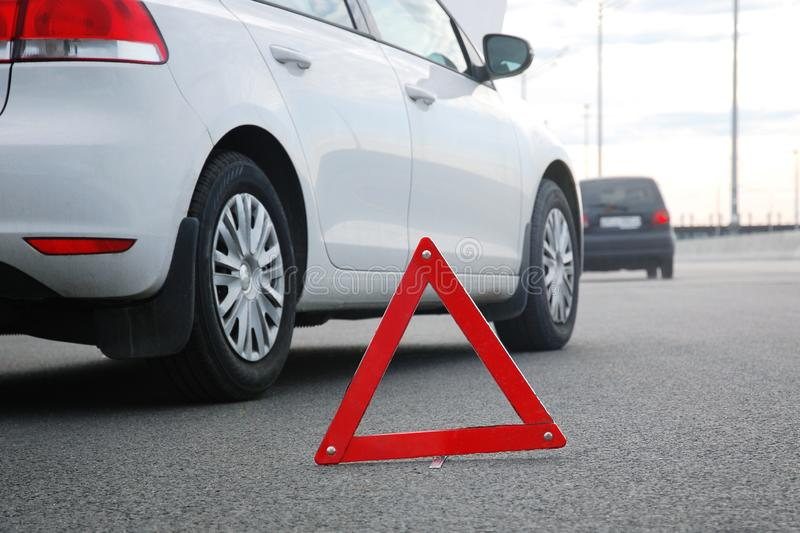 Road accident triangle. Cars on highway, low angle shot. Road accident or vehicle breakdown  -  two cars white and black stopped on highway after collision. Red stock photography