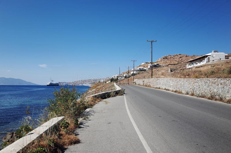 Road adjacent to the Sea. A straight road without any car adjacent to Aegean Sea, Mykonos, Greece stock photos