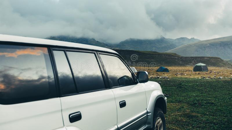 Road adventure concept. Car standing near tents on a camping in royalty free stock images